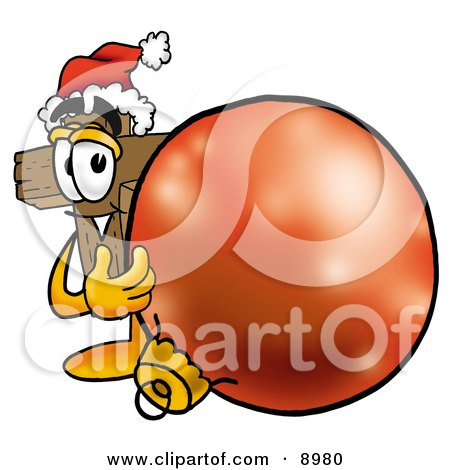 Clipart Picture of a Wooden Cross Mascot Cartoon Character Wearing a Santa Hat, Standing With a Christmas Bauble by Toons4Biz
