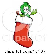 Dollar Sign Mascot Cartoon Character Wearing A Santa Hat Inside A Red Christmas Stocking by Toons4Biz