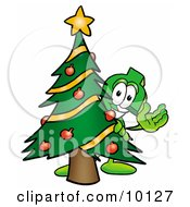 Dollar Sign Mascot Cartoon Character Waving And Standing By A Decorated Christmas Tree by Toons4Biz