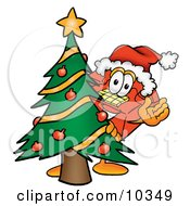 Clipart Picture Of A Red Telephone Mascot Cartoon Character Waving And Standing By A Decorated Christmas Tree