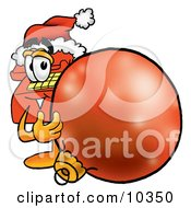 Clipart Picture Of A Red Telephone Mascot Cartoon Character Wearing A Santa Hat Standing With A Christmas Bauble by Toons4Biz