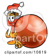 Clipart Picture Of A Paint Brush Mascot Cartoon Character Wearing A Santa Hat Standing With A Christmas Bauble by Toons4Biz