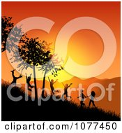 Silhouetted Children Playing On A Hillside At Sunset