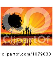 Silhouetted Walking Family Holding Hands By A Waterfront And Tree Against A Sunset