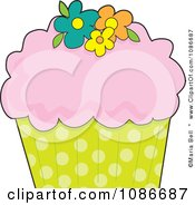 Pink Frosted Cupcake With Flowers And A Polka Dot Wrapper