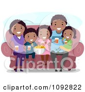 Happy Black Family Watching A Movie At Home And Eating Snacks