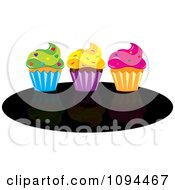 Cupcakes With Green Yellow And Pink Frosting And Sprinkles On A Black Oval