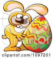 Happy Orange Easter Bunny Hugging A Decorated Egg