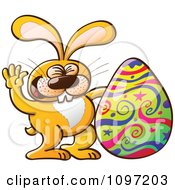 Happy Orange Easter Bunny Waving By A Decorated Egg