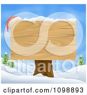 Santa Hat On The Corner Of A Wooden Christmas Sign In A Winter Landscape
