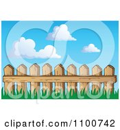 Wooden Picket Fence With Grass Against A Blue Sky With Clouds