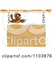 Clipart Christmas Robin With A Santa Hat Pointing On A Snow Covered Wooden Sign Royalty Free Vector Illustration