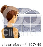 Rear View Of A Brunette Woman Looking Out A Window On A Rainy Day