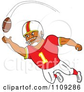 Black American Football Player Receiver In A Red Jersey Catching A Ball
