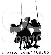 Silhouetted Girls Standing On A Swing
