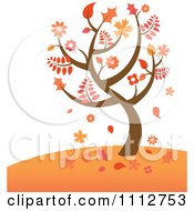 Autumn Tree With Falling Leaves On A Hill