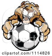 Clipart Friendly Cougar Mascot Holding Out A Soccer Ball Royalty Free Vector Illustration