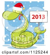 Cartoon Of A Happy Green Snake Wearing A Santa Hat And Holding A Year 2013 Sign In The Snow Royalty Free Vector Clipart by Hit Toon