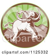 Clipart Of A Retro Attacking Elephant Over A Circle With Mountains Royalty Free Vector Illustration by patrimonio