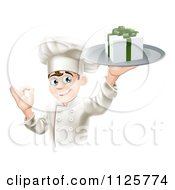 Clipart Of A Happy Chef Holding A Gift On A Platter And Gesturing Okay Royalty Free Vector Illustration