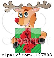Cartoon Of A Cute Happy Reindeer Holding A Christmas Present Royalty Free Vector Clipart by visekart