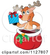 Cartoon Of A Cute Reindeer Holding A Gift Over A Sack Royalty Free Vector Clipart by visekart
