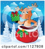 Cartoon Of A Cute Reindeer Holding A Present Over A Sack In The Snow Royalty Free Vector Clipart
