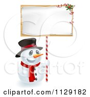 Cartoon Of A Happy Christmas Snowman Holding Up A Festive Sign Royalty Free Vector Clipart