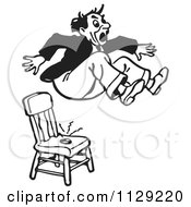 Cartoon Of A Black And White Retro Surprised Pranked Man Jumping Out Of A Shock Chair Vector Clipart by Picsburg