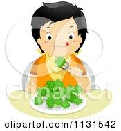 Hungry Asian Boy Eating Broccoli