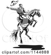 Clipart Of A Retro Black And White Rodeo Cowboy On A Bucking Horse 2 Royalty Free Vector Illustration