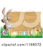 Cartoon Of A Brown Bunny Pointing To A Wooden Sign Over Easter Eggs In Grass Royalty Free Vector Clipart