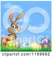 Cartoon Of A Grinning Easter Bunny With Eggs And A Basket In Grass Over Blue Sky Royalty Free Vector Clipart