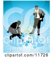 Two Businessmen Completing A Blue Jigsaw Puzzle Together