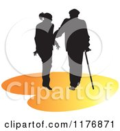 Clipart Of A Silhouetted Caring Nurse Walking With A Man And A Cane On An Orange Heart Royalty Free Vector Illustration by Lal Perera