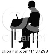 Cartoon Of A Black Silhouetted Man Working On A Laptop At A Desk Royalty Free Vector Clipart
