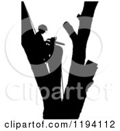 Cartoon Of A Silhouetted Remorseful Arborist In A Branchless Tree With A Chain Saw Royalty Free Vector Clipart