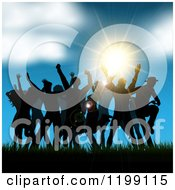 Silhouetted People Dancing In Grass Against A Sunset And Blue Sky