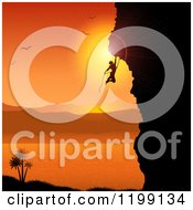 Silhouetted Rock Mountain Climber Against An Orange Tropical Sunset And Bay