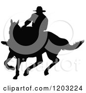 Clipart Of A Black Silhouetted Horseback Cowboy Swinging A Whip Royalty Free Vector Illustration