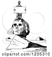 Cartoon Of A Vintage Black And White Man Holding A Sign On The Egyptian Sphinx Royalty Free Vector Clipart
