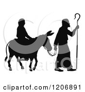 Clipart Of A Silhouette Of Mary And Joseph With A Donkey Nativity Scene Royalty Free Vector Illustration