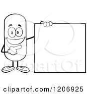 Cartoon Of A Black And White Happy Pill Mascot Standing By A Sign Royalty Free Vector Clipart by Hit Toon