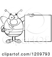 Cartoon Of A Black And White Happy Bee Mascot Pointing To A Sign Royalty Free Vector Clipart