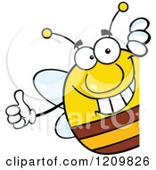 Cartoon Of A Happy Bee Holding A Thumb Up Around A Sign Royalty Free Vector Clipart