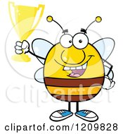 Cartoon Of A Successful Bee Holding Up A Trophy Royalty Free Vector Clipart