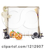 Halloween Mummy Pointing To A White Board Sign With Pumpkins Black Cats And A Broomstick
