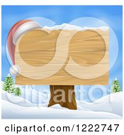 Wooden Christmas Sign With A Santa Hat In A Winter Landscape Over Blue Sky