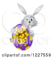Clipart Of A Gray Bunny Holding An Easter Egg Royalty Free Vector Illustration