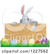 Clipart Of A Gray Bunny Over A Wood Sign And Easter Eggs Royalty Free Vector Illustration by AtStockIllustration